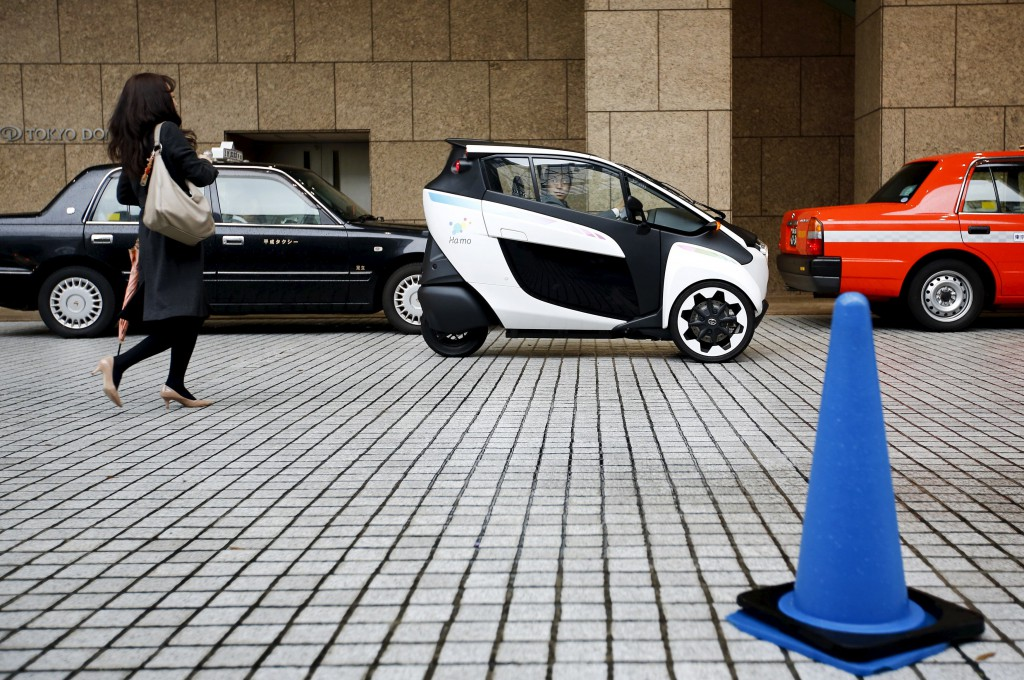 A Toyota i-Road electric vehicle parks outside a hotel in Tokyo