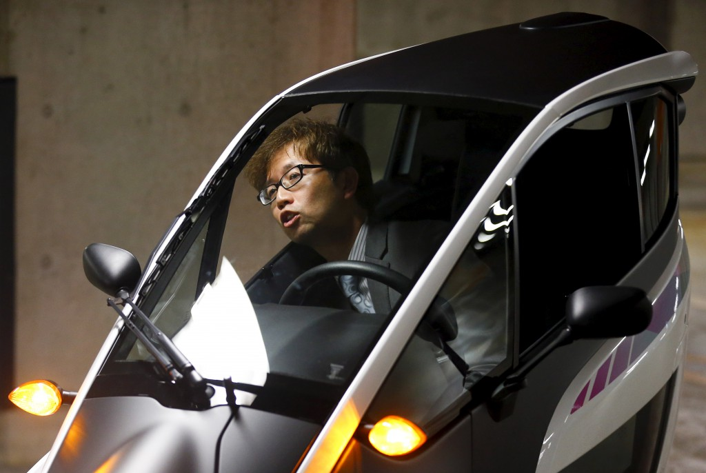 Toyota's i-Road chief engineer Yanaka sits in an electric vehicle in Tokyo